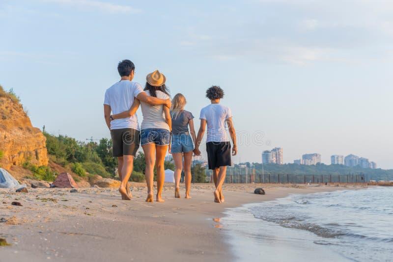 Grupp av vänner som promenerar en strand på sommartid Lyckliga ungdomarsom tycker om en dag på stranden fotografering för bildbyråer