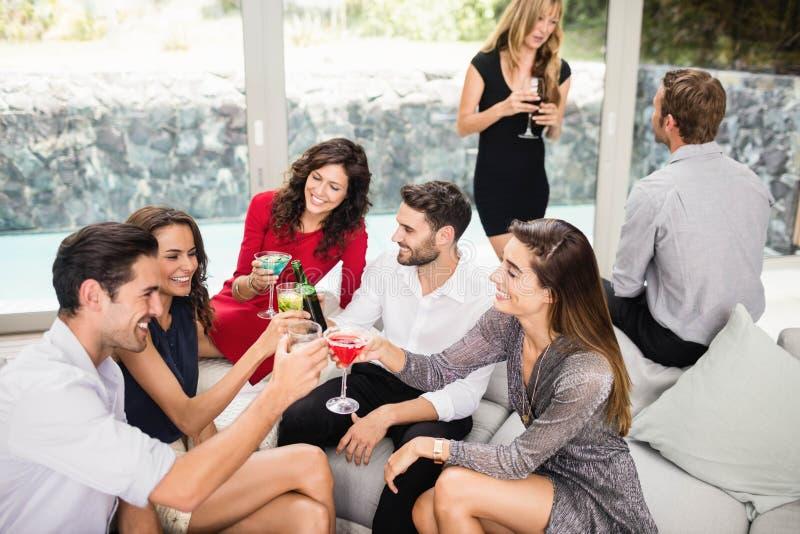 Grupp av vänner som rostar coctaildrinkar fotografering för bildbyråer