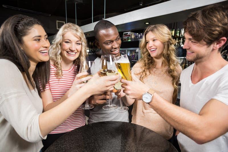 Grupp av vänner som rostar med öl och vin royaltyfri fotografi