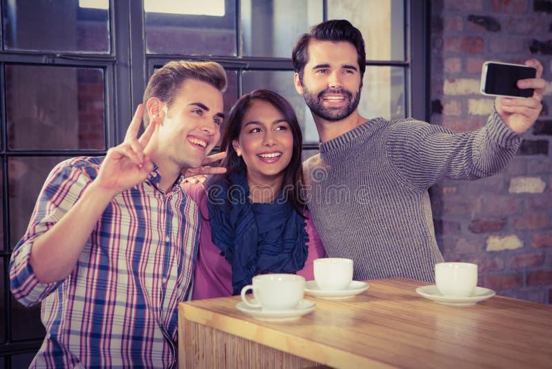 Grupp av vänner som ser deras smartphone fotografering för bildbyråer