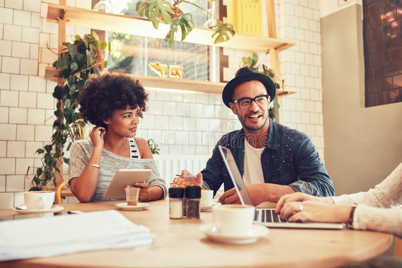 Grupp av vänner som sitter i en coffee shop med bärbara datorn royaltyfri foto