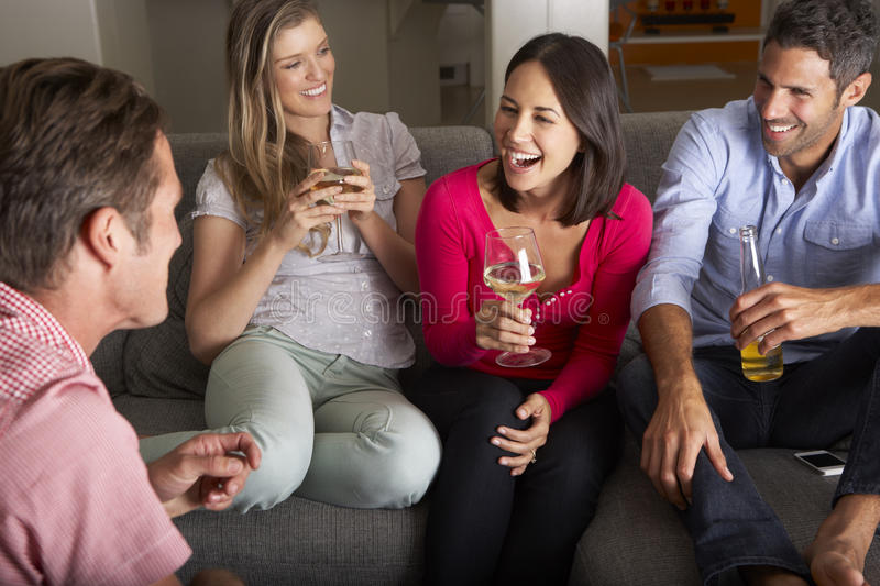 Grupp av vänner som sitter på Sofa Talking And Drinking Wine royaltyfri bild