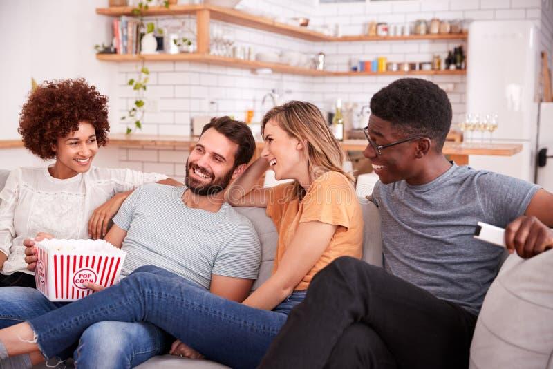 Grupp av vänner som sitter på Sofa And Watching Movie At den hem- stunden som äter popcorn royaltyfri fotografi