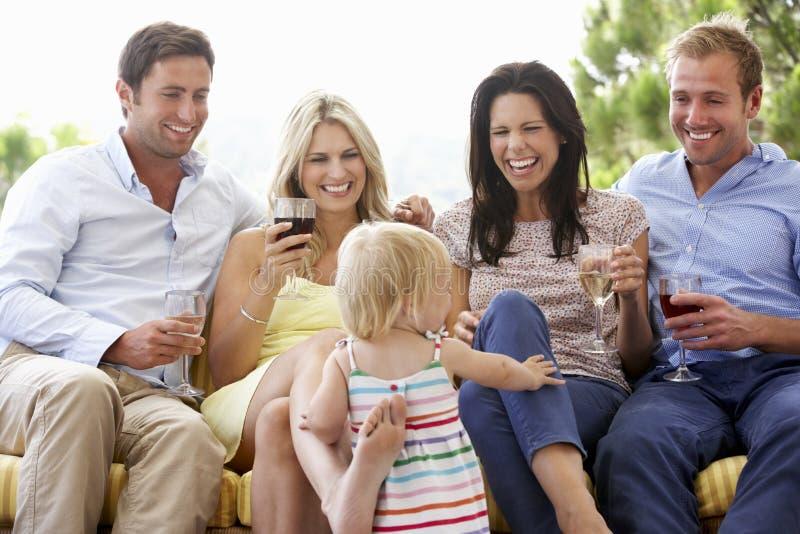 Grupp av vänner som sitter på utomhus- Seat samman med unga Gir arkivbild