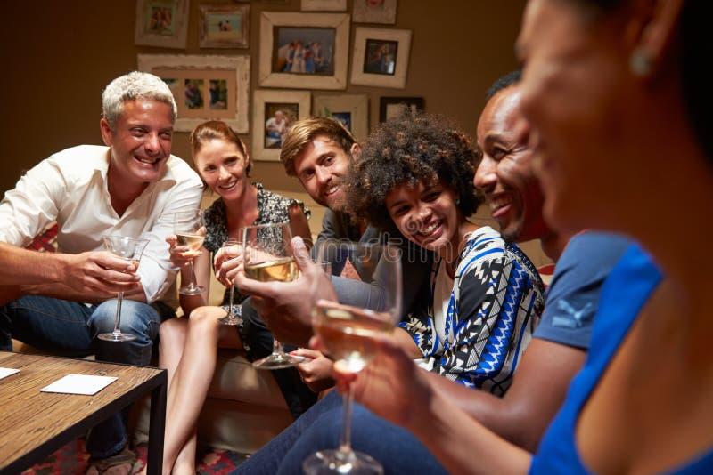 Grupp av vänner som sitter runt om en tabell på huspartiet fotografering för bildbyråer