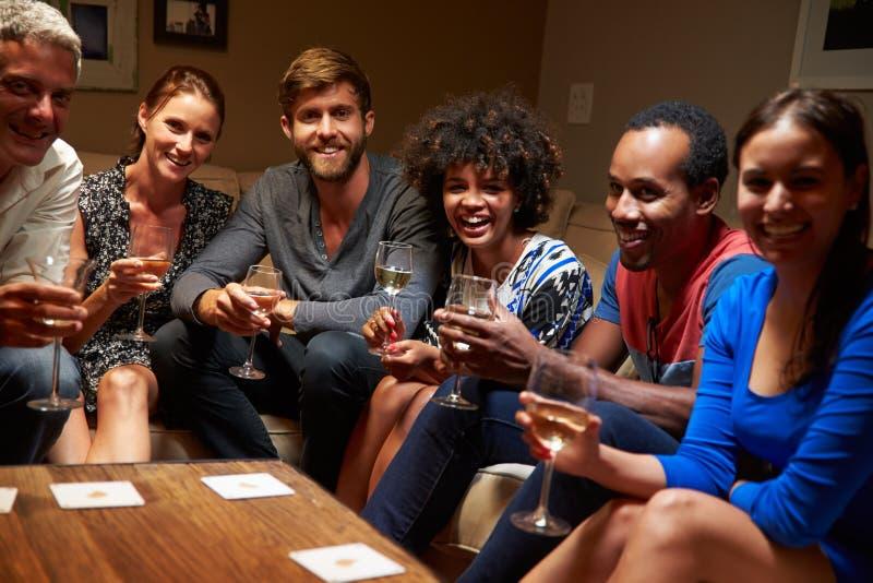 Grupp av vänner som sitter runt om en tabell på huspartiet royaltyfri fotografi