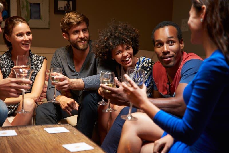 Grupp av vänner som sitter runt om en tabell på huspartiet royaltyfria bilder