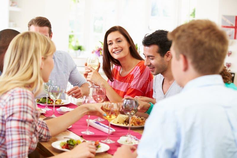 Grupp av vänner som sitter runt om tabellen som har matställepartiet royaltyfri bild