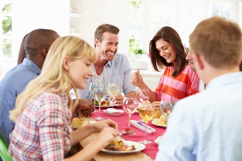 Grupp av vänner som sitter runt om tabellen som har matställepartiet arkivbild