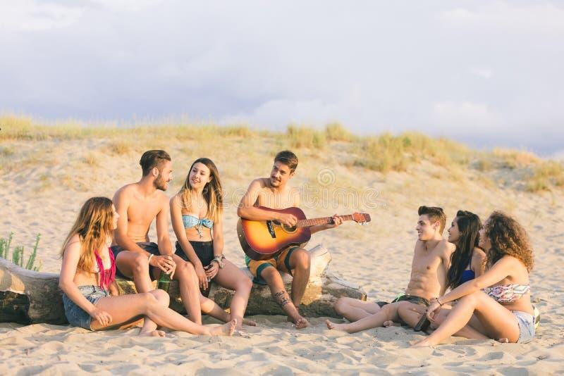 Grupp av vänner som sjunger på stranden på solnedgången royaltyfria foton