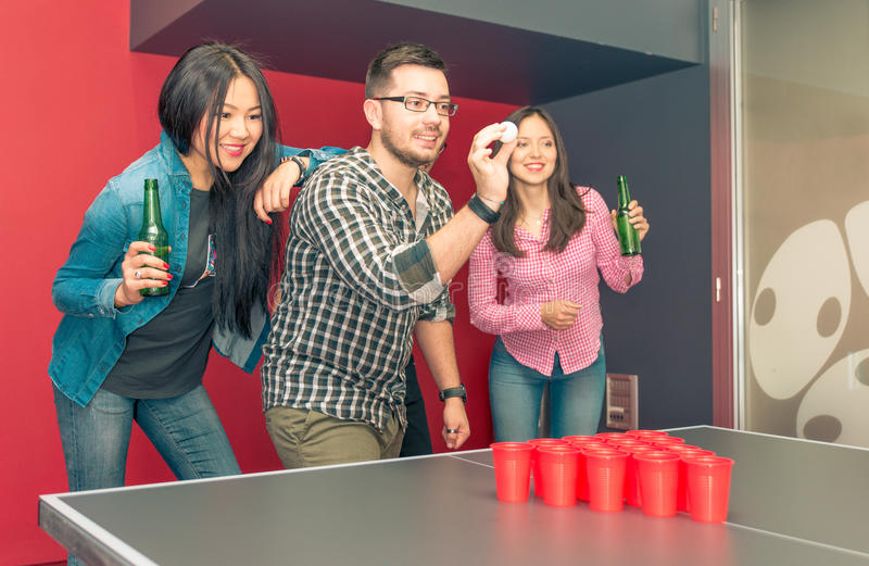 Grupp av vänner som spelar ölpong royaltyfri bild
