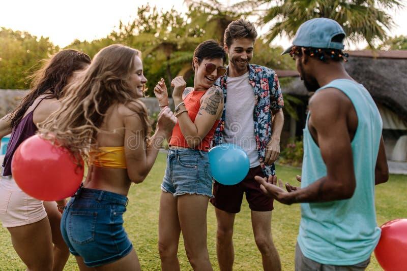 Grupp av vänner som spelar ballongen som brister leken på partiet arkivbild