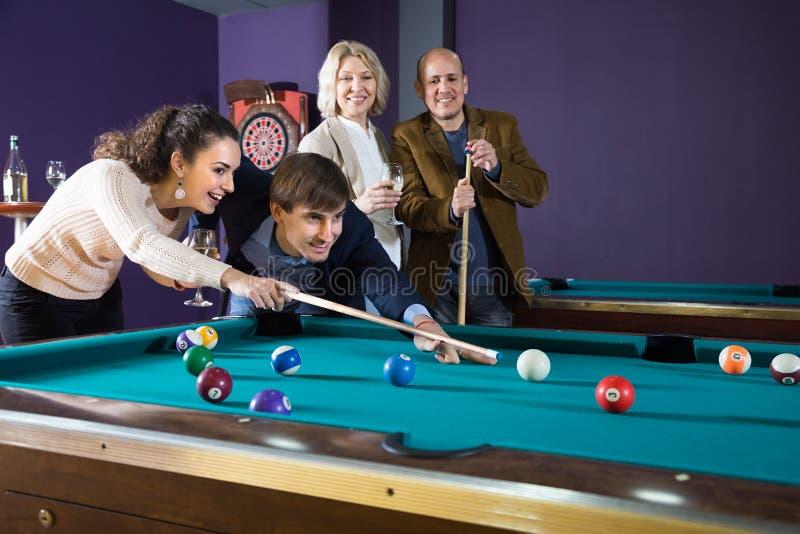 Grupp av vänner som spelar biljard och ler i billiardrum royaltyfria foton