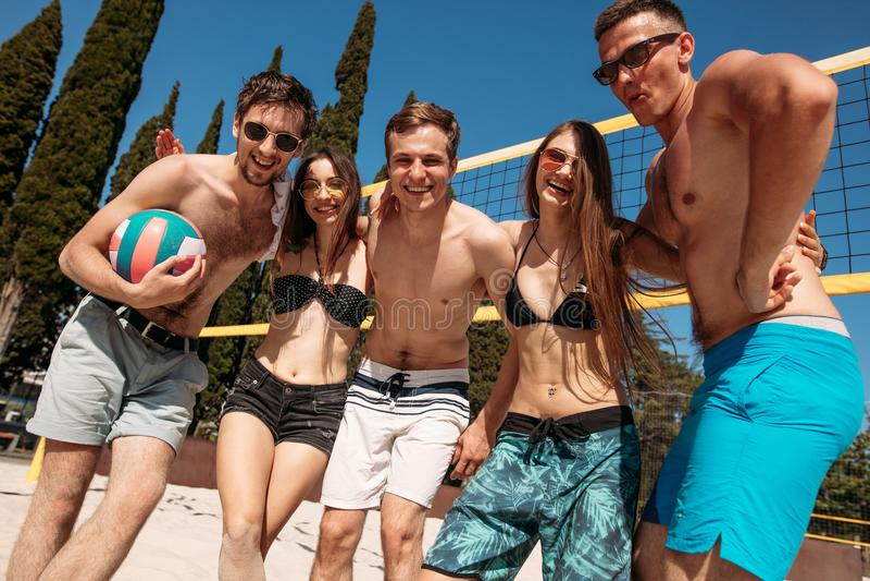 Grupp av vänner som spelar strandsalvan - Mång--etik grupp människor som har gyckel på stranden fotografering för bildbyråer
