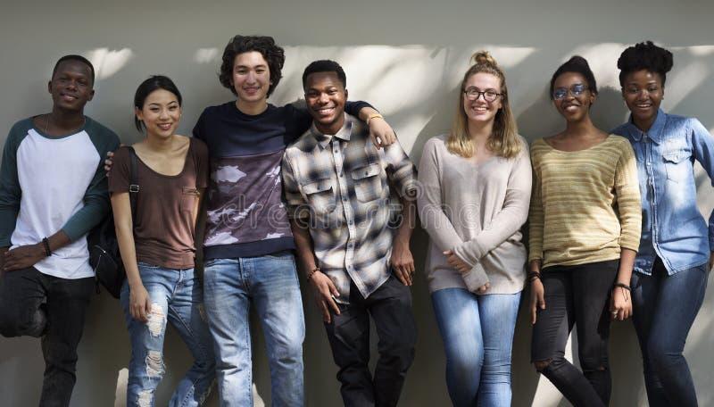 Grupp av vänner som står som ler royaltyfri bild