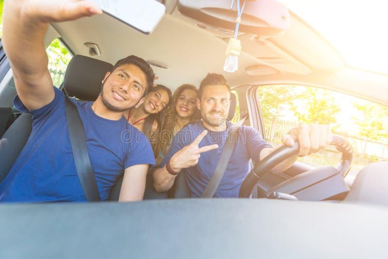 Grupp av vänner som tar en selfie in i bilen arkivfoto