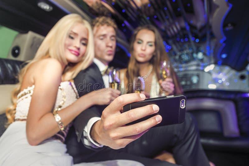 Grupp av vänner som tar en selfie i limousine arkivbilder
