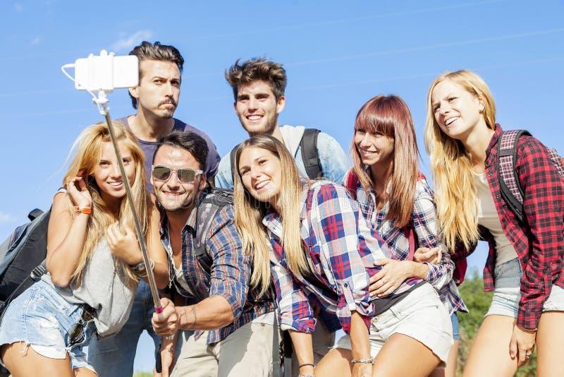 Grupp av vänner som tar en självstående royaltyfria bilder
