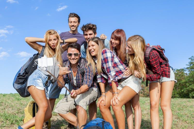 Grupp av vänner som tar en självstående arkivbild