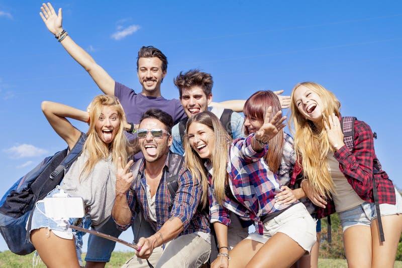 Grupp av vänner som tar en självstående med selfiepinnen royaltyfri bild