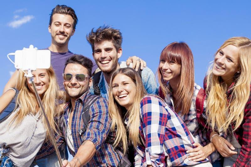 Grupp av vänner som tar en självstående med selfiepinnen arkivfoton