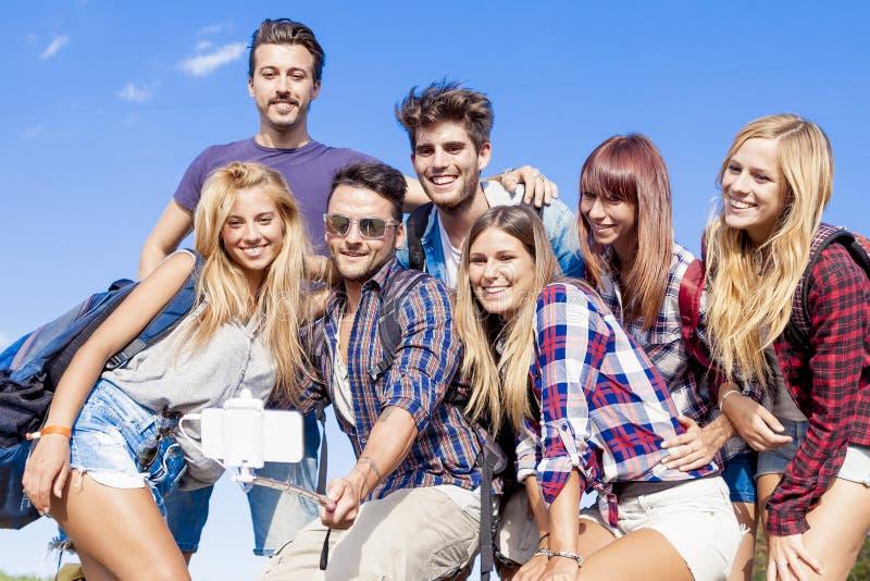 Grupp av vänner som tar en självstående med selfiepinnen arkivbilder