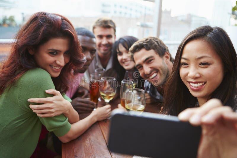 Grupp av vänner som tar fotografiet på den utomhus- takstången royaltyfri foto