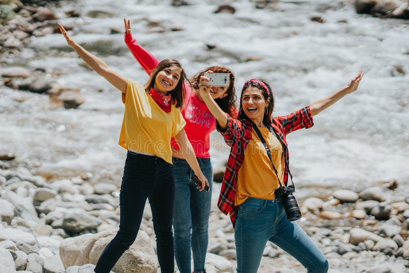 Grupp av vänner som tar selfie nära strömmen fotografering för bildbyråer