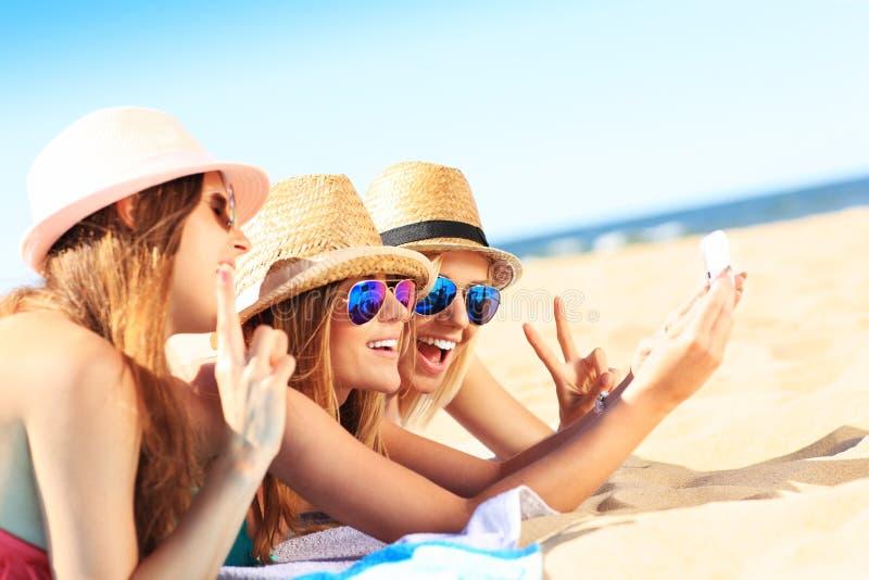 Grupp av vänner som tar selfie på stranden arkivfoto