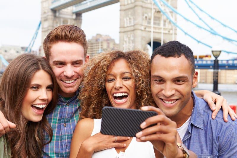 Grupp av vänner som tar Selfie vid tornbron i London royaltyfri fotografi