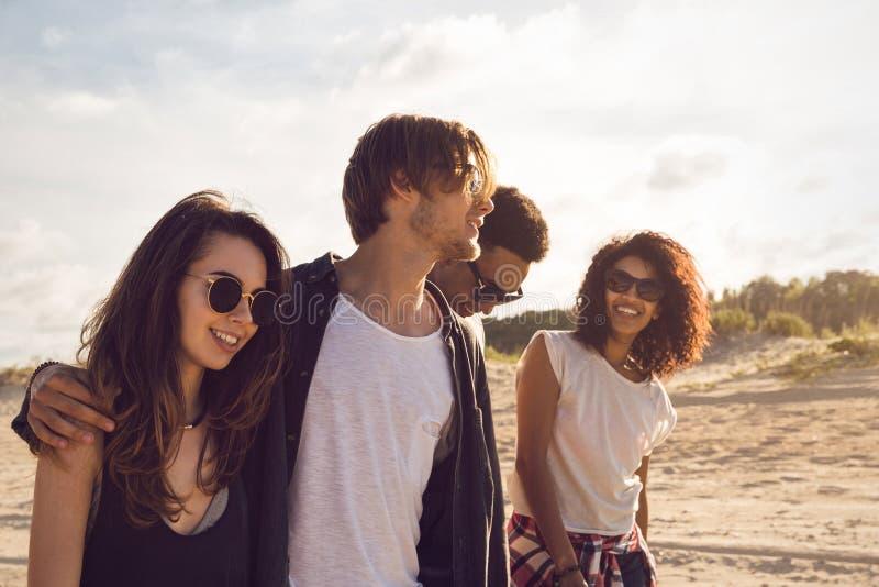 Grupp av vänner som tillsammans går på stranden royaltyfria foton