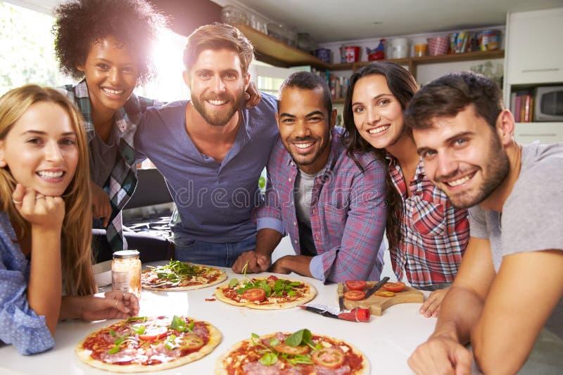 Grupp av vänner som tillsammans gör pizza i kök arkivfoto
