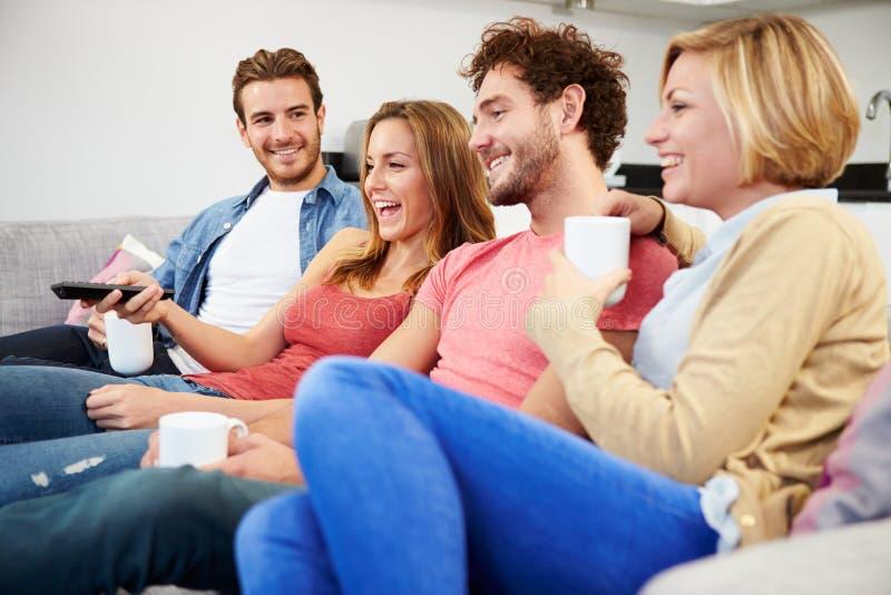 Grupp av vänner som tillsammans håller ögonen på television hemma arkivfoto