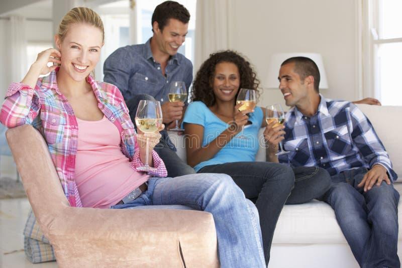 Grupp av vänner som tillsammans kopplar av på Sofa Drinking Wine At Home arkivbild