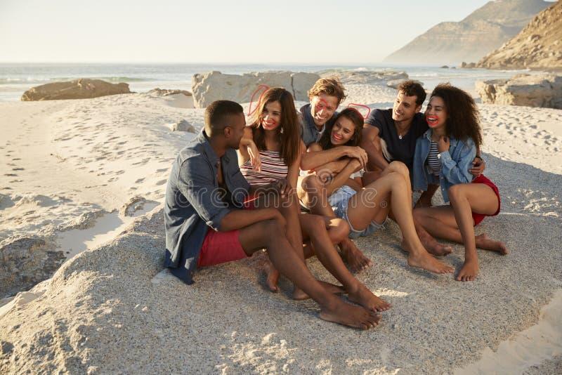Grupp av vänner som tillsammans kopplar av på strandsemester royaltyfri foto