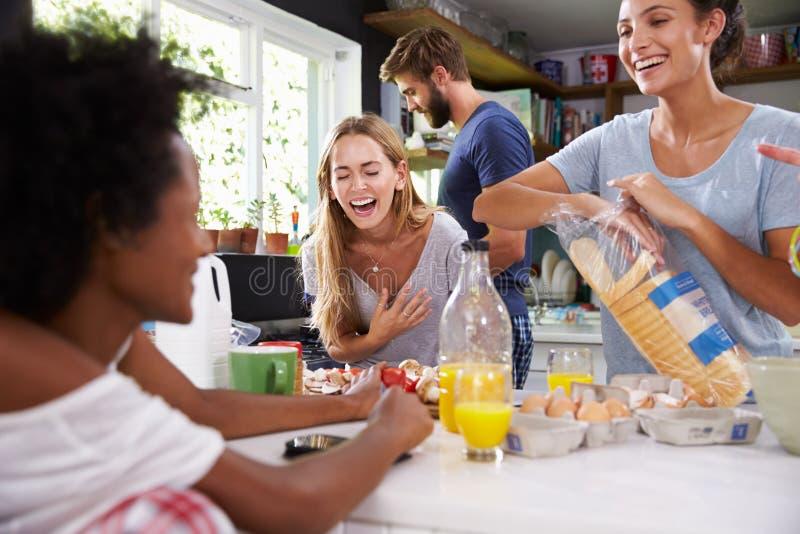 Grupp av vänner som tillsammans lagar mat frukosten i kök royaltyfri fotografi