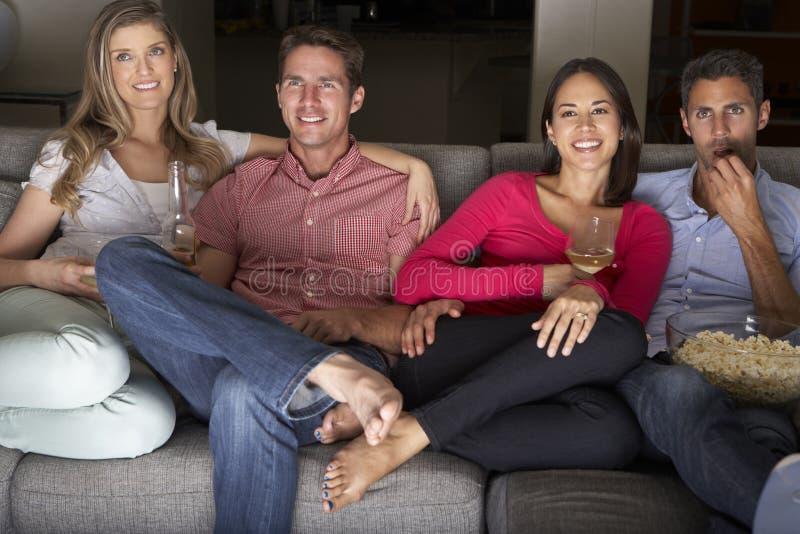 Grupp av vänner som tillsammans sitter på Sofa Watching TV royaltyfri bild