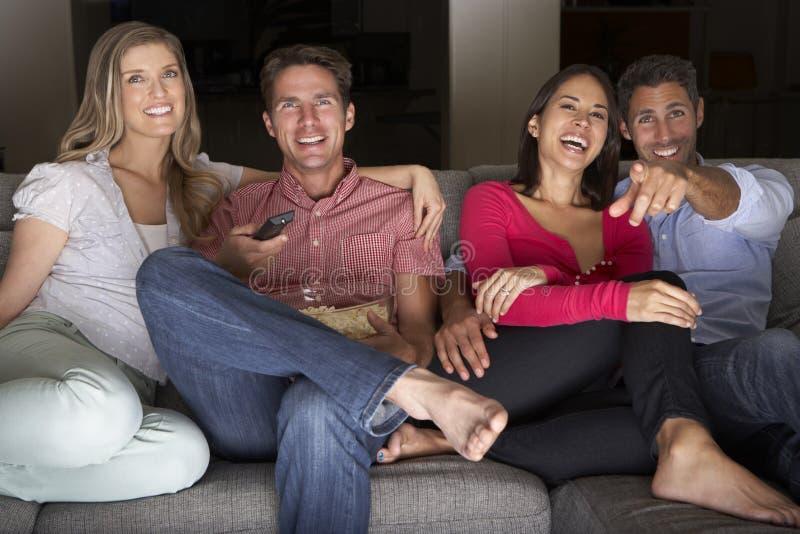 Grupp av vänner som tillsammans sitter på Sofa Watching TV arkivbild
