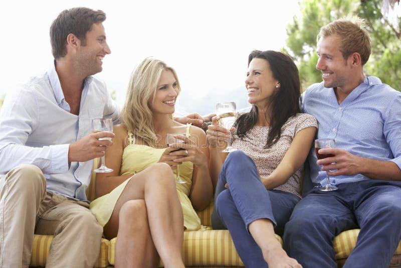 Grupp av vänner som tillsammans sitter på utomhus- Seat royaltyfri foto