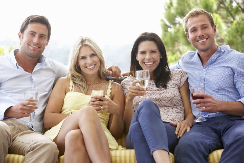 Grupp av vänner som tillsammans sitter på utomhus- Seat fotografering för bildbyråer