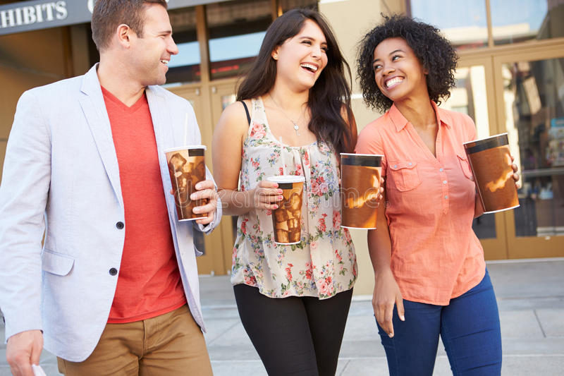 Grupp av vänner som tillsammans står utanför bio arkivfoto