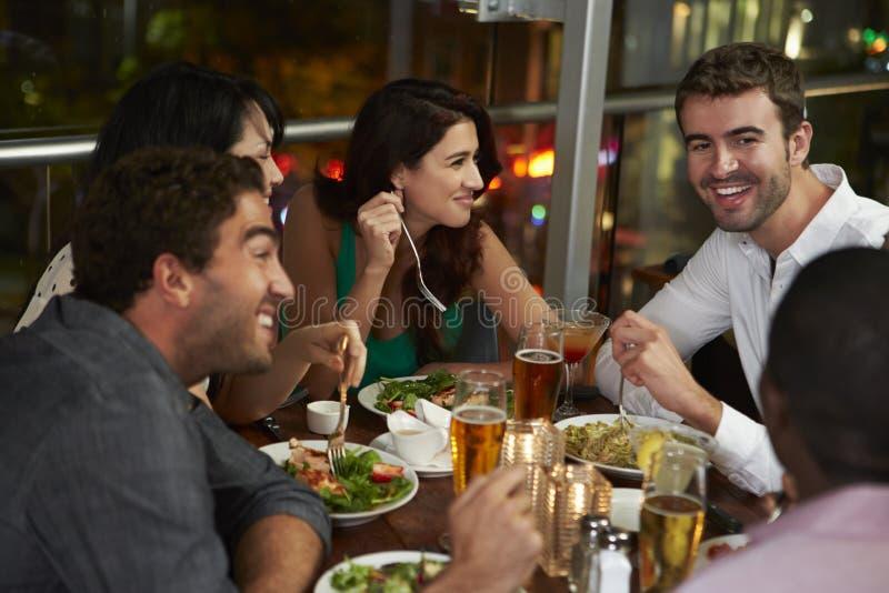 Grupp av vänner som tycker om aftonmål i restaurang royaltyfria foton