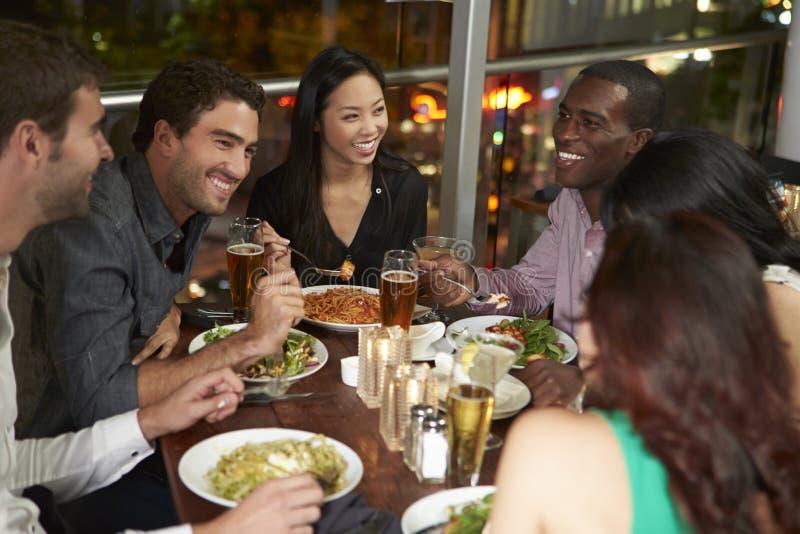 Grupp av vänner som tycker om aftonmål i restaurang royaltyfri fotografi