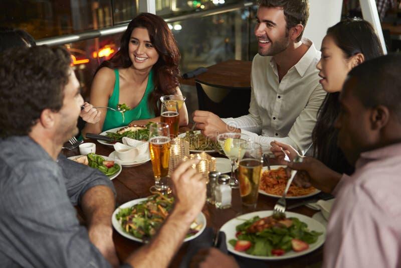 Grupp av vänner som tycker om aftonmål i restaurang arkivfoto