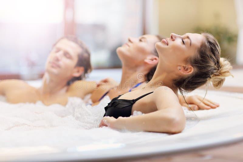 Grupp av vänner som tycker om bubbelpoolen i hotellbrunnsort royaltyfria foton
