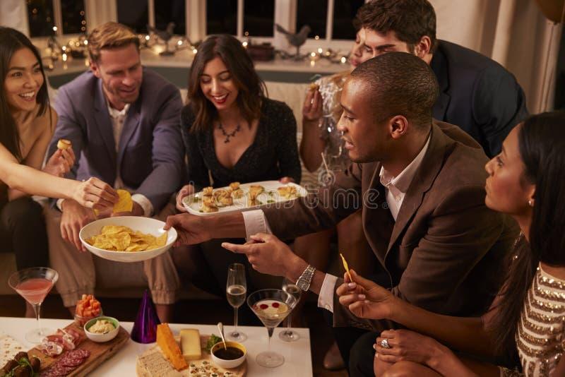 Grupp av vänner som tycker om drinkar och mellanmål på partiet arkivbild