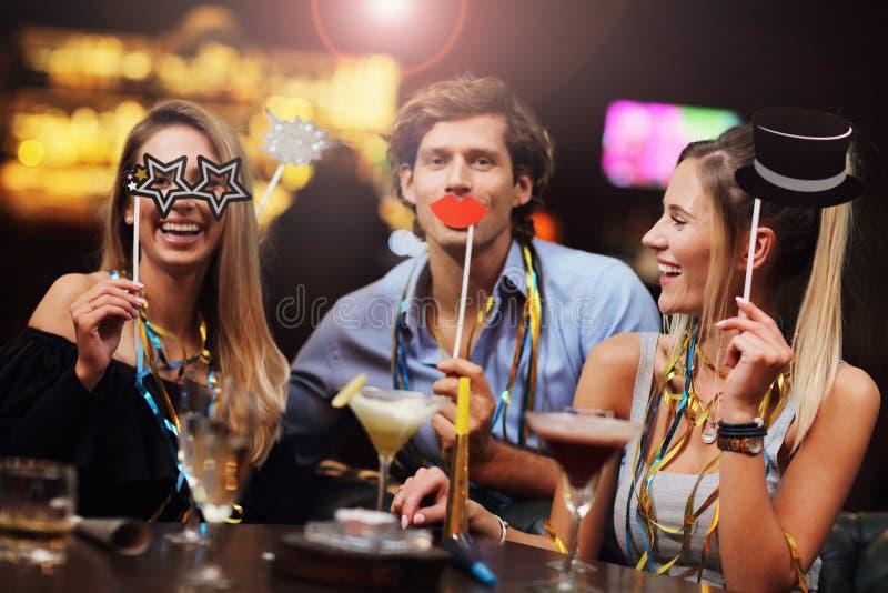 Grupp av vänner som tycker om drinken i stång arkivfoto