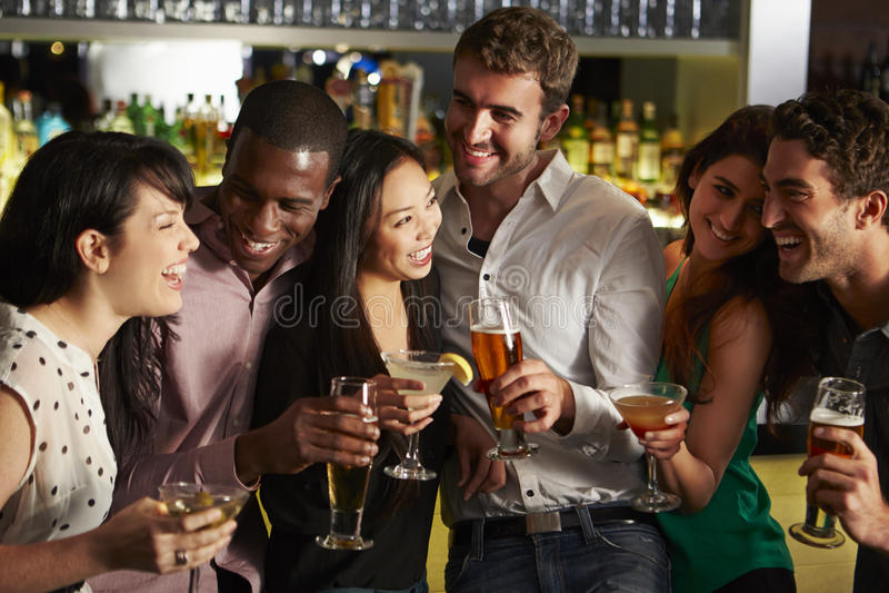 Grupp av vänner som tycker om drinken i stång royaltyfri bild
