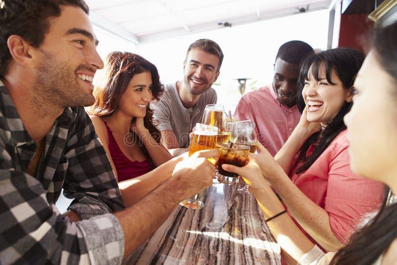 Grupp av vänner som tycker om drinken på den utomhus- takstången arkivfoton