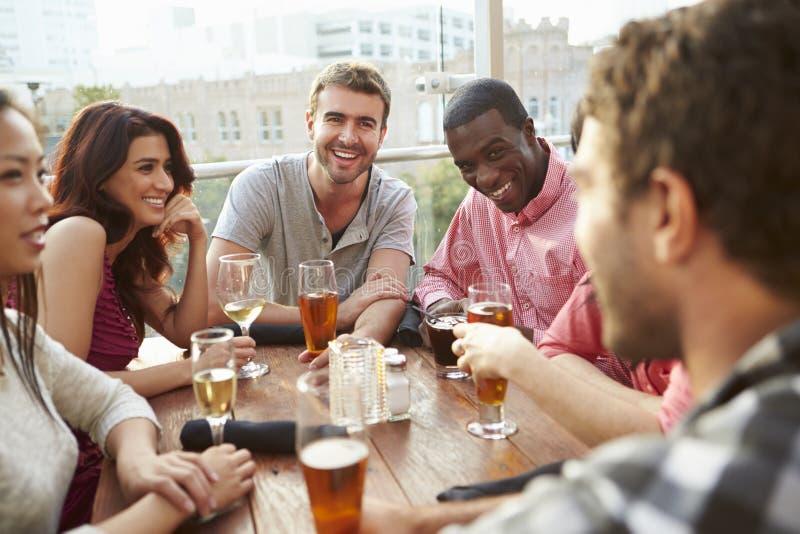 Grupp av vänner som tycker om drinken på den utomhus- takstången royaltyfri fotografi